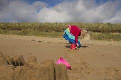 Een jong meisje die op het strand op een de zomersdag spelen stock afbeelding