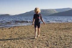 Een jong meisje die op het strand op een de zomersdag spelen royalty-vrije stock foto's