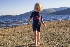 Een jong meisje die op het strand op een de zomersdag spelen stock foto