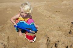 Een jong meisje die op het strand op een de zomersdag spelen royalty-vrije stock afbeelding