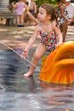 Het jonge meisje spelen in water stock afbeeldingen