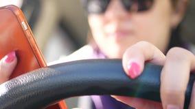 Een jong meisje drijft een auto, onderzoekt de telefoon, telefoneert een tweede hand, houdt andere het stuurwiel stock footage