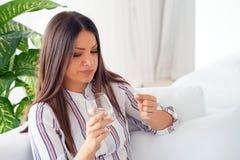 Een jong meisje drinkt een pil van pijn royalty-vrije stock foto