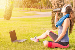 Een jong meisje in een park op het gras na geschiktheid opleiding met laptop en hoofdtelefoons en zij drinkt eiwitschok 23 royalty-vrije stock fotografie