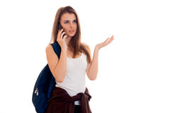 Een jong meisje in een t-shirt en met een rugzak op de schouder met een ernstige persoon die op de telefoon spreken Royalty-vrije Stock Afbeeldingen