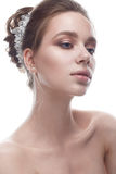 Een jong meisje in een zacht huwelijksbeeld met een diadeem op haar hoofd Het mooie model in het beeld van de bruid op een wit is Stock Foto's