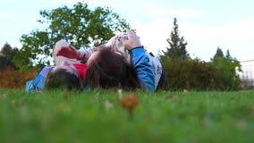 Een jong meisje en een kerel die op het gazon liggen stock videobeelden