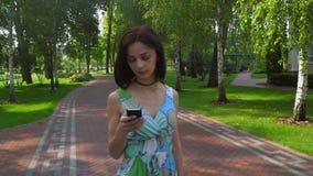 Een jong meisje gaat op een weg in het park en het bereiken van een bericht op de telefoon stock videobeelden