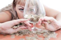 Een jong meisje, geld, en een glasdrinkbeker Stock Foto's