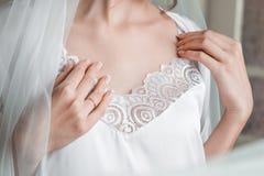Een jong meisje in een gevoelige witte lingerie toont haar schoonheid royalty-vrije stock foto