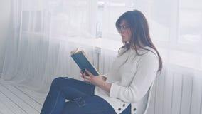 Een jong meisje in glazen zit op een stoel en leest een boek stock videobeelden