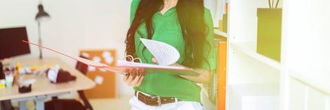 Een jong meisje in het bureau houdt een omslag met documenten royalty-vrije stock afbeelding