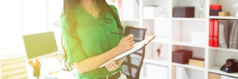 Een jong meisje in het bureau houdt een potlood en een blad voor nota's royalty-vrije stock foto's