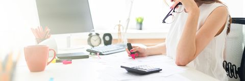 Een jong meisje in het bureau houdt een roze teller, glazen en werkt met de documentatie stock foto's
