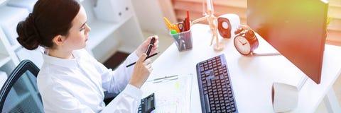 Een jong meisje in het bureau zit bij een lijst, houdt een teller en een potlood in haar hand en werkt met een computer, a royalty-vrije stock fotografie