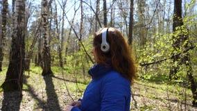 Een jong meisje in het Park die aan muziek in hoofdtelefoons luisteren Een vrouw loopt door het de lentepark en geniet van de muz stock footage