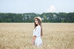 Een jong meisje in een hoed is boatman die van de aard van een tarwegebied genieten Mooi meisje in witte kledingslooppas op het g royalty-vrije stock foto