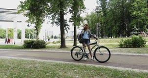 Een jong meisje houdt een fiets en spreekt aan haar mobiele telefoon in het park stock video