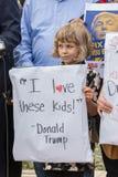 Een jong meisje houdt een teken I liefde deze jonge geitjes van Donald Trump citeren royalty-vrije stock fotografie