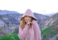 Een jong meisje in een kap drukt haar vinger aan haar lippen en kijkt mysteriously royalty-vrije stock foto
