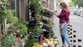 Een jong meisje kiest bloemen in een bloemwinkel op de straat stock video