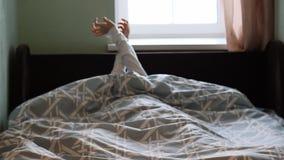 Een jong meisje ligt in bed en wekt omhoog vroeg omhoog het nippen van haar handen in de ochtend stock video