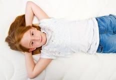 Een Jong meisje ligt op het bed Kwaliteitsmatras stock afbeeldingen