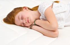 Een Jong meisje ligt op het bed Kwaliteitsmatras Royalty-vrije Stock Afbeeldingen