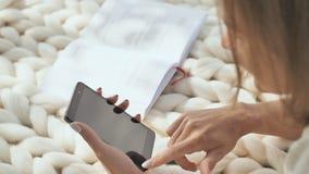 Een jong meisje ligt op een witte plaid in het park en draait een bericht op de telefoon stock video