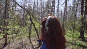Een jong meisje loopt in het Park in de middag Meisje die aan muziek door hoofdtelefoons luisteren Gezonde Levensstijl stock video