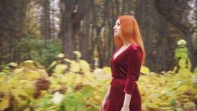 Een jong meisje loopt in het park en glimlacht stock video