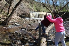 Een jong meisje loopt met haar kind bij de waterval stock afbeelding