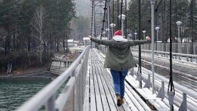 Een jong meisje loopt over de brug over de rivier aan het park, genietend van het leven en vrijheid Langzame motie, 1920x1080 stock video