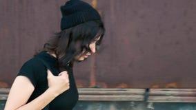 Een jong meisje loopt voorzichtig, kijkend rond en leunend tegen een oude roestige muur stock videobeelden