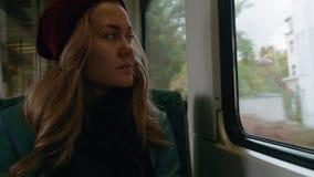 Een jong meisje met blauwe ogen berijdt op een metro of tramtrein Zij is vermoeid en ontspannen Langzame Motie stock videobeelden