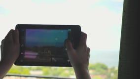 Een jong meisje met blonde die een tablet gebruiken neemt beelden en video's van het landschap buiten het venster stock video