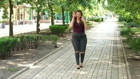 Een jong meisje met bovenmatig gewicht loopt in het Park en het spreken op de telefoon stock footage