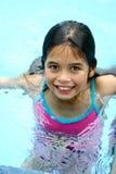Een jong meisje met bruine ogen geniet van zijnd in het zwembad stock foto's