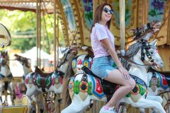 Een jong meisje met glazen die op een carrouselpaarden berijden stock foto