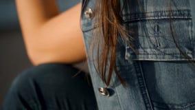 Een jong meisje met glazen zit op de stappen Fladderend haar in het windclose-up stock footage