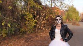 Een jong meisje met een griezelige samenstelling in de vorm van een schedel op een lege weg stock videobeelden