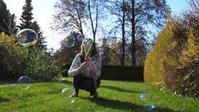 Een jong meisje met een kind die in het Park op het gazon spelen Het meisje maakt zeepbels, en het kind vangt hen A stock footage