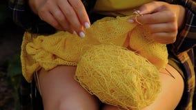Een jong meisje met lang blond haar breekt een gele trui in de tuin in de zomer. vrouw maakt kleren met handen dicht stock video
