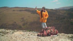 Een jong meisje met lang donker haar in een geel jasje en een grijs GLB bevindt zich op een berg en neemt een selfie op de telefo stock videobeelden