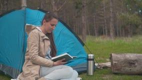 Een jong meisje met lang haar zit dichtbij een blauwe tent in het bos en leest een boek stock video