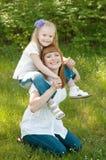 Een jong meisje met mather op een groen gras Stock Afbeeldingen