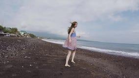 Een jong meisje in een mooie kleding loopt en kijkt rond het zwarte strand van vulkanisch zand aan Bali stock video