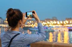 Een jong meisje neemt beelden van een nachtstad met een camera van de celtelefoon stock fotografie