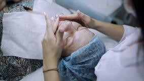 Een jong meisje ontvangt behandeling voor acne medisch masker op gezicht met probleemhuid stock video