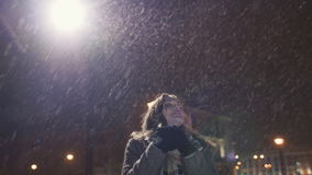Een jong meisje op de achtergrond van avondstad warmt koude handen op Gezien stadslichten het sneeuwen stock videobeelden